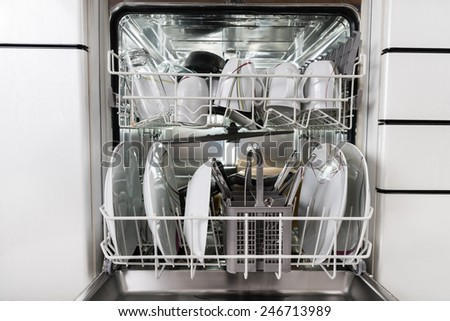 Photo Of Utensils Arranged In Dishwasher In Kitchen - stock photo