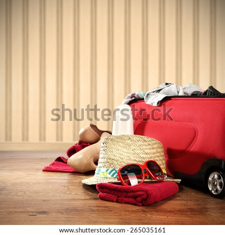 photo of vacation time and red suitcase on floor  - stock photo