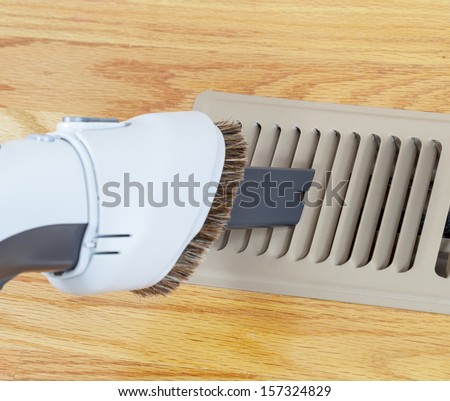 photo of vacuum cleaning heater floor vent with Red Oak Floors in background  - stock photo