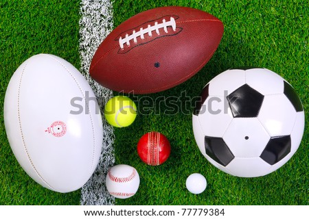 Photo of various sports balls on a grass next to the white line, shot from above. - stock photo