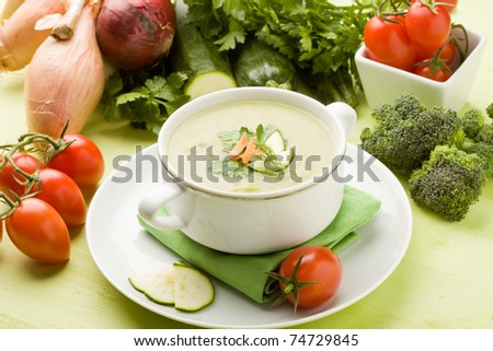 photo of vegetarian vegetable soup on green wooden table with different vegetables around