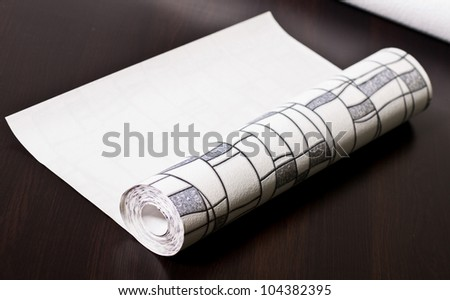 Photo of wallpaper roll laying on a table - stock photo