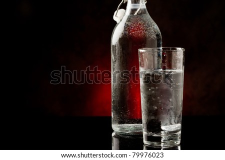 photo of water glass and bottle standing on black glass table - stock photo