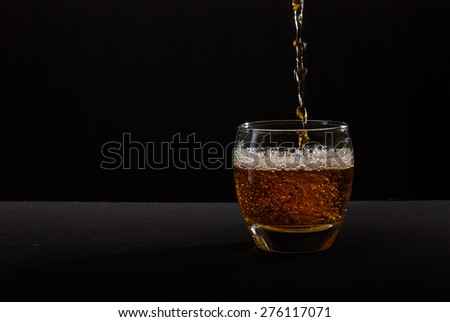 Photo of whiskey pouring into glass against black background - stock photo