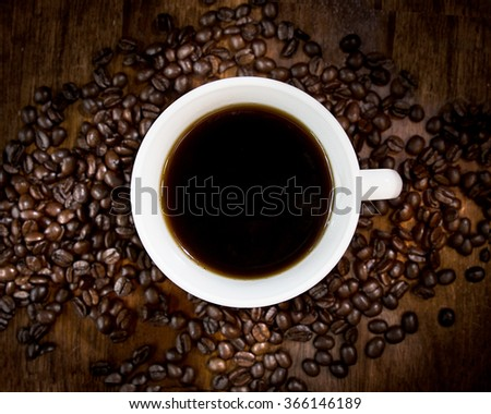 photo of white coffee cup centered in the middle of coffee beans, taken from above - stock photo