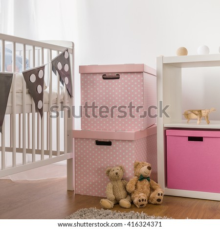 Photo of white cot and pink boxes in child bedroom - stock photo