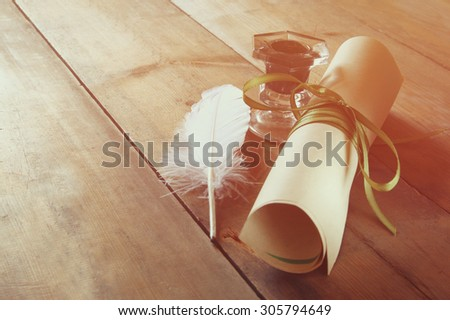 photo of white Feather, inkwell and scroll paper on old wooden table. retro filtered image - stock photo