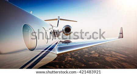 Photo of White Luxury Generic Design Private Jet Flying in Blue Sky at sunset.Uninhabited Desert Mountains Background.Business Travel Picture.Horizontal,Film Effect. 3D rendering - stock photo