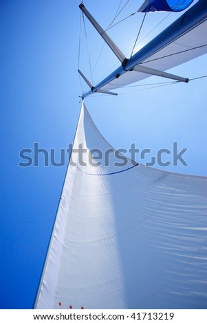 Photo of white sails of yachts on the background of blue sky. Photographed from the bottom up (Low Angle View). - stock photo