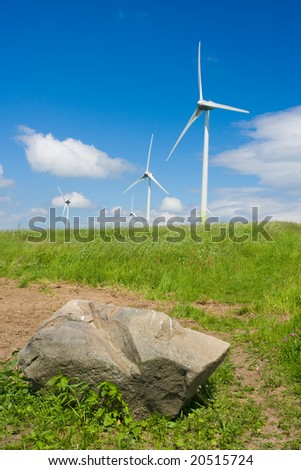 Photo of Wind power installation and rock in sunny day