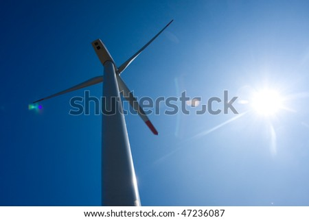 Photo of Wind power silhouette installation in sunny day - stock photo