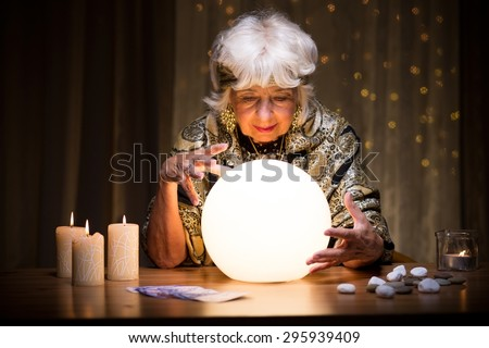 Photo of woman foretelling future from crystal ball - stock photo