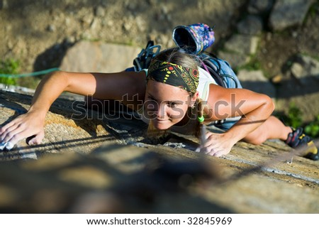 Photo of woman heartily climbing on mountain - stock photo