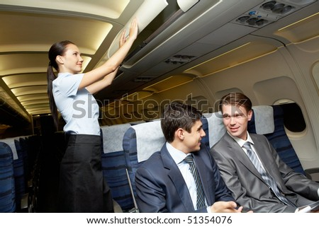 Photo of woman holding and giving glass of water to young businessman - stock photo