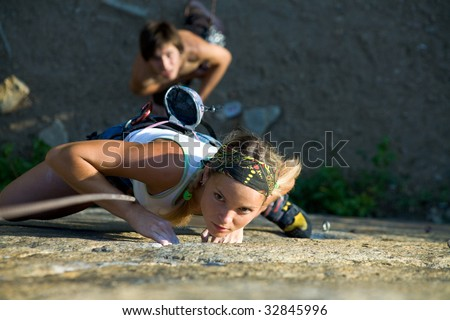 Photo of woman in sport wear climbing up mountain - stock photo