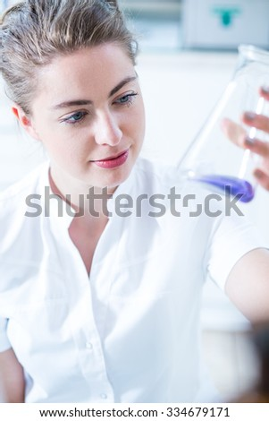 Photo of woman scientist holding glass utensil with sample