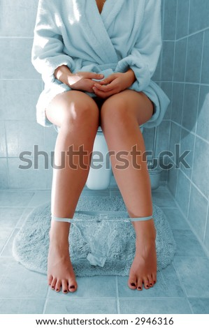 Photo of woman sitting on a toilet. - stock photo