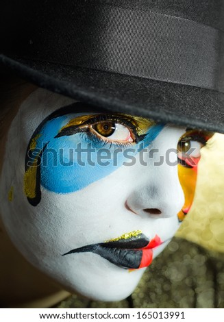 Photo of woman with a mask makeup in a hat - stock photo