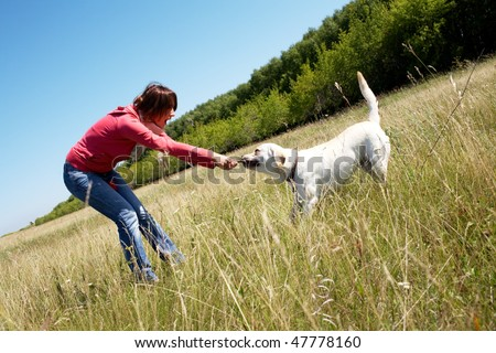 Photo of woman with her dog pulling branch - stock photo