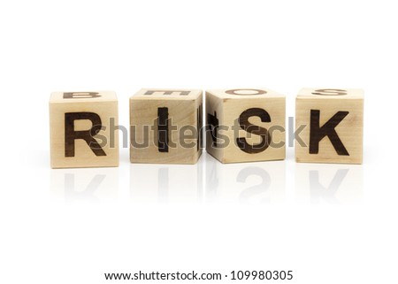 Photo of wooden letter blocks forming the word Risk on the white background with reflection - stock photo