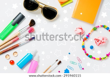 Photo of workplace with lots of stationery objects and glasses. Bright studio shot on light background with star. - stock photo