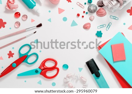 Photo of workplace with lots of stationery objects and shells. Bright studio shot on light background with dots. - stock photo