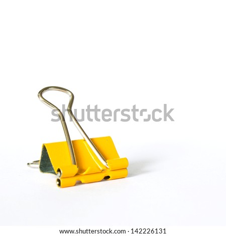 Photo of Yellow metal paperclips on white background - stock photo