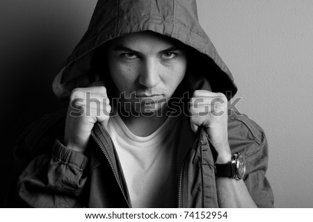 Photo of young adult male wearing hood, threatening expression on face. - stock photo