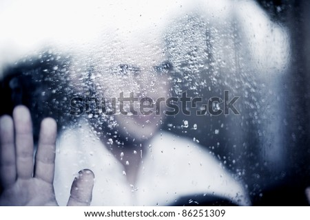 photo of young adult man standing at the window on a rainy day. focus on the raindrops on the glass. toned image - stock photo