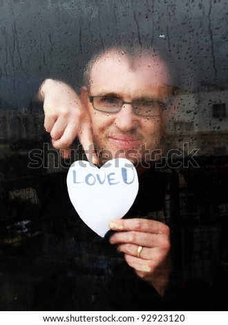 photo of young adult man standing at the window on a rainy day with paper heart - stock photo