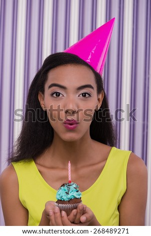 Photo of young african-american woman looking at camera. Woman wearing birthday hat and holding small cupcake with candle. Concept for happy birthday - stock photo