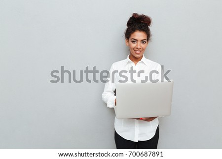 Photo of young african cheerful business woman standing over grey wall with laptop computer. Looking camera.