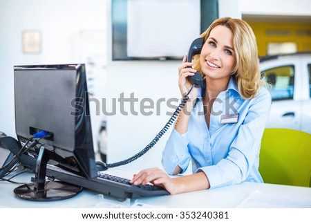 Photo of young beautiful business woman in car showroom. Young business woman working with computer and talking on phone. Modern office interior