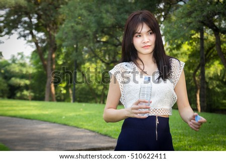 Photo of Young beautiful  woman wearing white shirts drinking water at summer green park