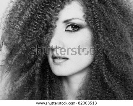 Photo of young beautiful woman with magnificent curly hair - stock photo