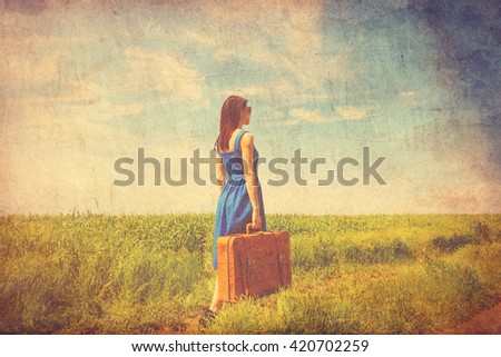 photo of young beautiful woman with suitcase in the field - stock photo