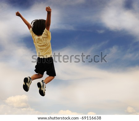 Photo of young boy jumping and raising hands up - stock photo