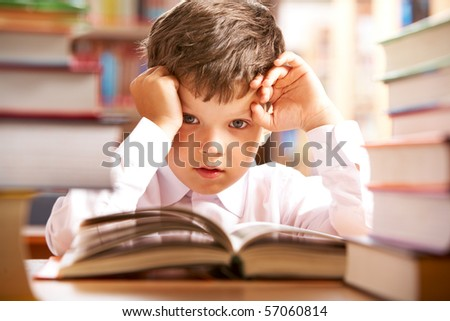 Photo of young boy looking at camera while reading book