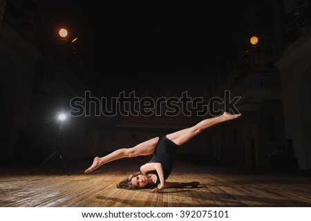 Photo of young brunette dancer girl in split jump on stage in theater with spotlight. ballet dancer in black clothes. barefoot dancer. - stock photo
