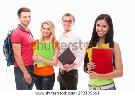 Photo of young brunette student smiling. Girl with document cases in her hands posing in front of her collegues.