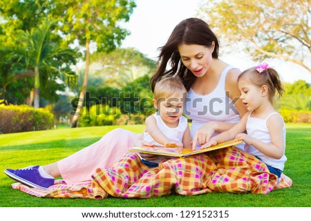Photo of young brunette woman teaching two sweet kids, cheerful mother with cute daughter and lovely son read interesting fairytale, children enjoying book on backyard in daycare, spring season - stock photo