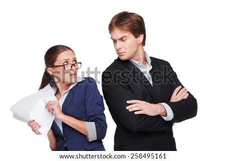 Photo of young business woman and man. Boss looking strictly at his scared assistant. Isolated on white background - stock photo