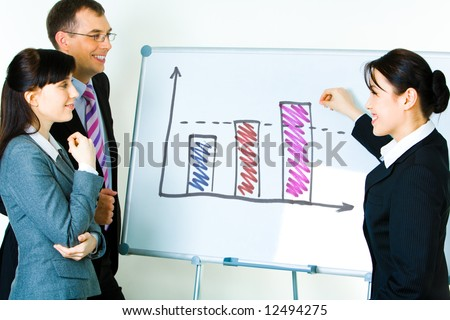 Photo of young businesswoman showing something on whiteboard with smile while her colleagues looking at it - stock photo