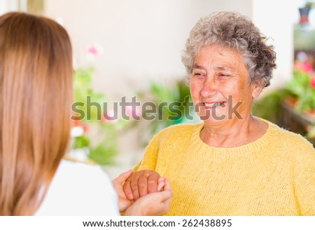 Photo of young carer holding the elderly woman hands - stock photo