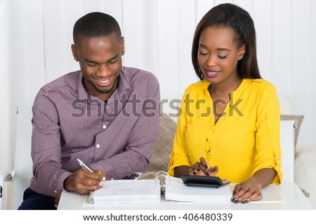Photo Of Young Couple Calculating Bill At Home - stock photo
