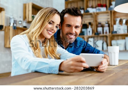 Photo of young couple taking selfie at cafe - stock photo