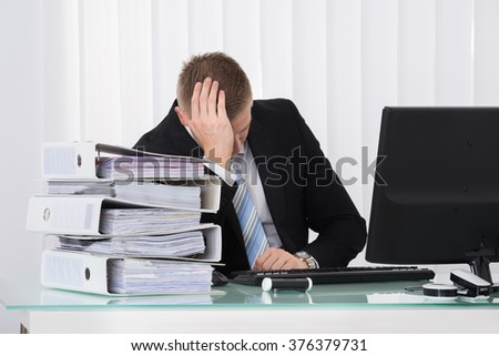 Photo Of Young Depressed Businessman Sitting In Office