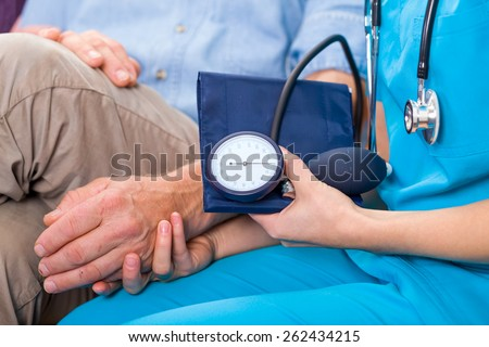 Photo of young doctor measures the blood pressure - stock photo