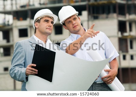 Photo of young engineer showing something to his colleague during meeting at building site - stock photo