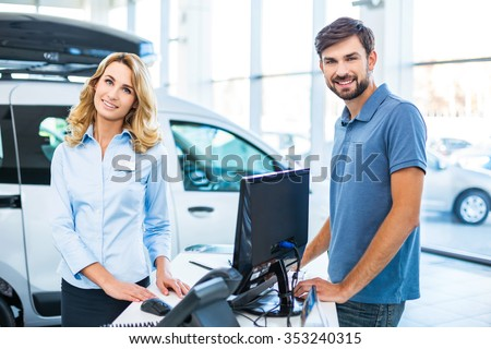 Photo of young female consultant and buyer. Young man buying new car in car showroom